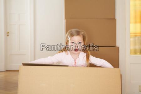 girl carrying large cardboard box
