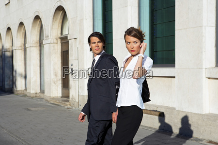 businessman and woman walking on street