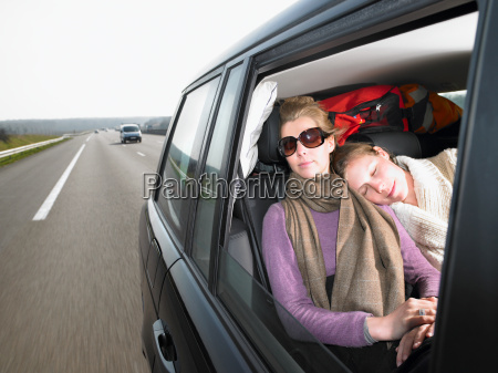 young women sleeping in car