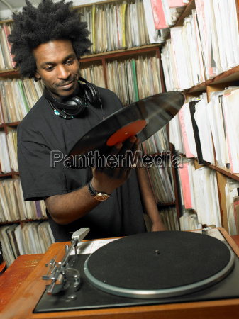 male dj holding record in music