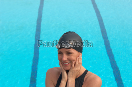 female swimmer standing by pool smiling