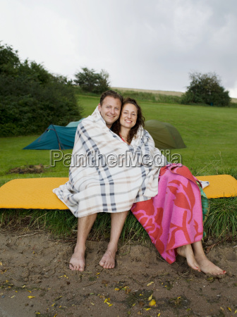 man and woman sitting under blanket