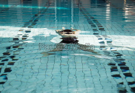 mature man swimming underwater in pool