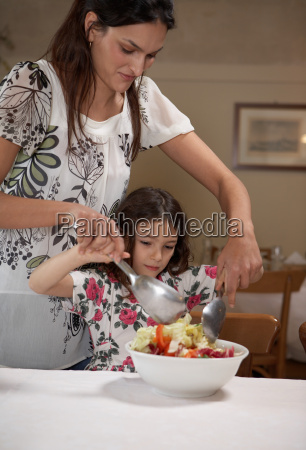 woman, helping, daughter, to, toss, salad - 18245430