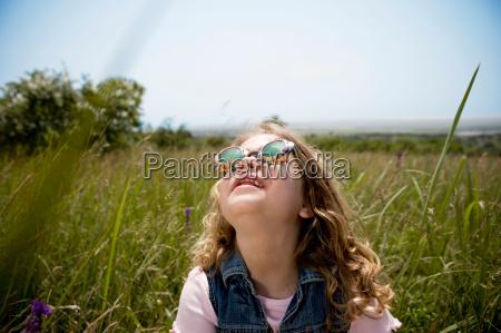 girl looking up at sun