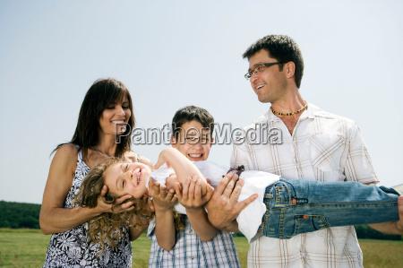 family holding little girl for portrait