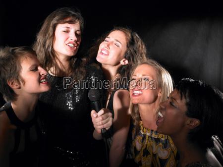 group of women singing karaoke