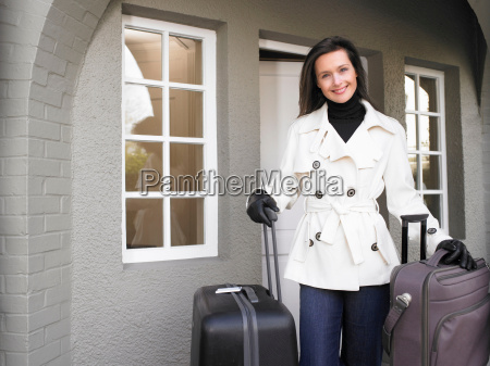 woman holding suitcases on the patio