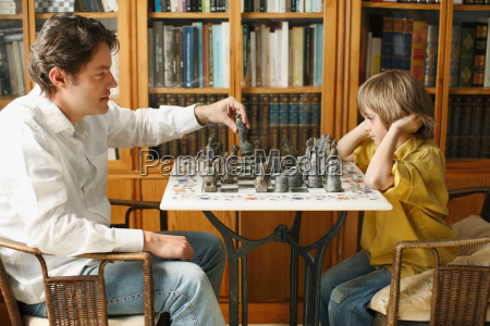 father playing chess with young boy