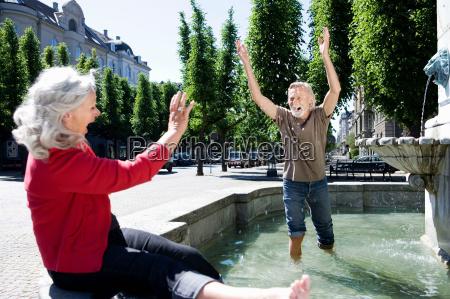 man throwing water at woman