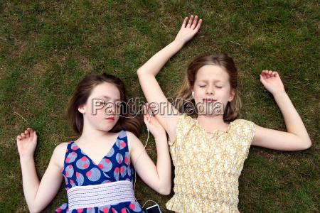 girls lying on grass with earphones
