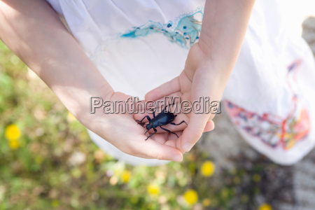 a young girl holding a beetle