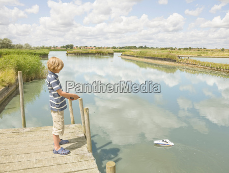 boy playing with a toy boat