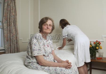 krankenschwester machen bett fuer aeltere frau