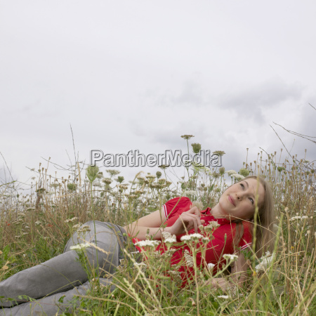 young woman lying in high grass
