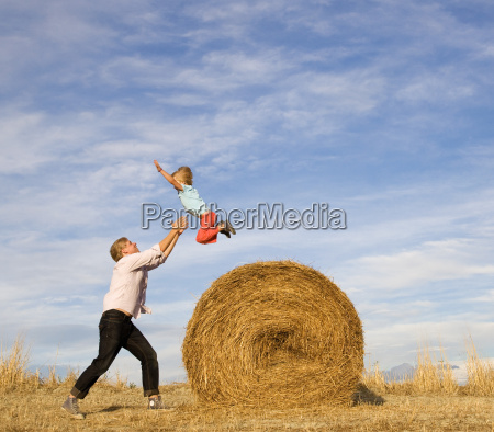 man catching boy jumping from hay