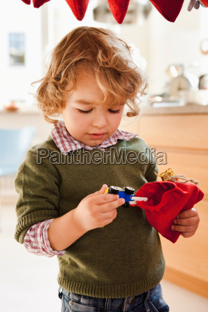 young boy pulling toy out of
