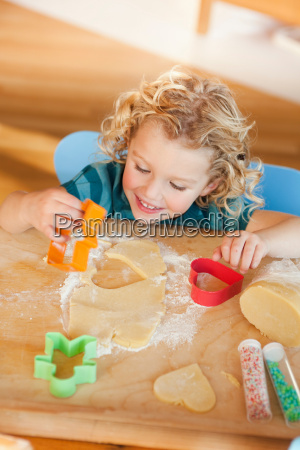 young girl cutting cookies