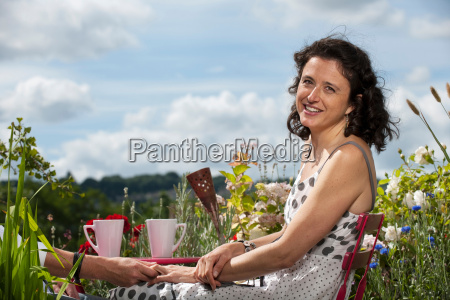 woman sitting on balcony holding hand