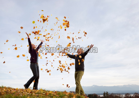 woman and man throwing autumn leaves