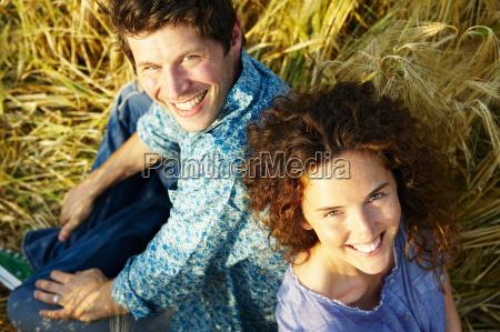 paar, sitzt, in, einem, weizenfeld, lächelnd - 18249080