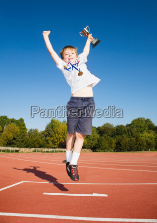 boy with medals and trophy at