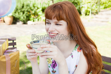 young woman holding tea cup smiling