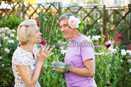 woman laughs at man with rose