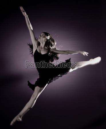 girl jumping in spotlight