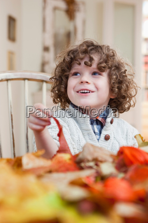 young boy playing with leaves