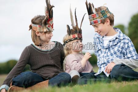 kinder in indianer kopfbedeckung