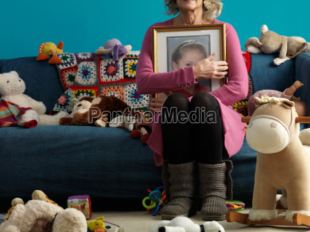 mature woman holding picture of child