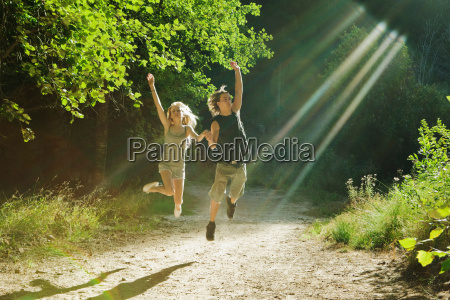 young couple jumping in forest