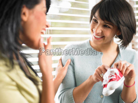 woman showing baby shoes to her