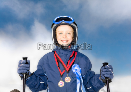 boy wearing medals and with skis