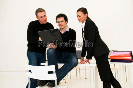 three business people look at laptop