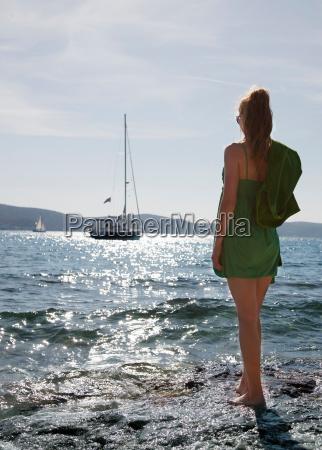 woman at beach looking at yacht