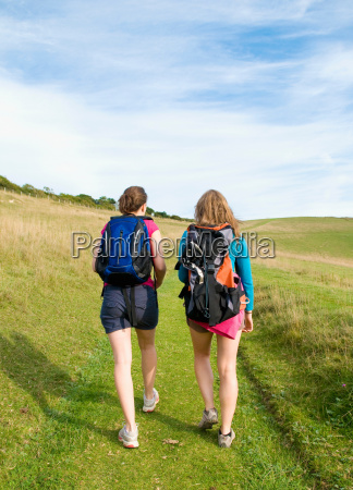 two young women hikers climb up