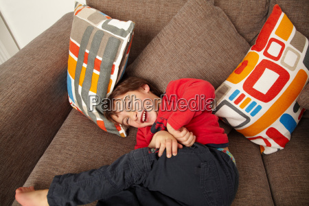 young boy laughing on sofa