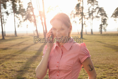 tattooed women in nature with cellphone