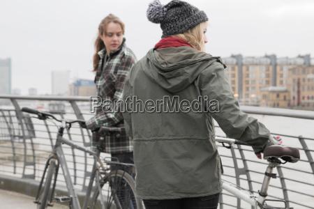 2 young women pushing bikes