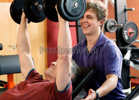 trainer helping man lift weights at