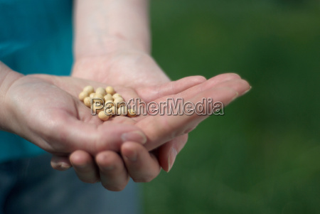 woman holding handful of seeds