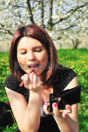 woman applying lipstick in park