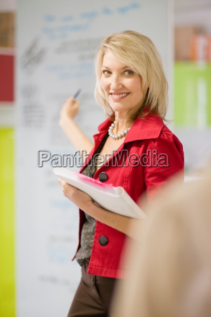 businesswoman pointing to office board