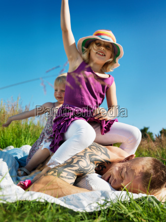 children sitting on father outdoors