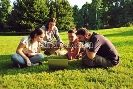 friends using laptop in grass in