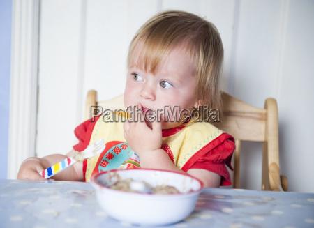 toddler girl in bib eating at