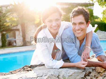 smiling couple hugging by pool