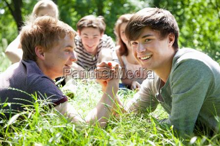 teenage boys arm wrestling in grass